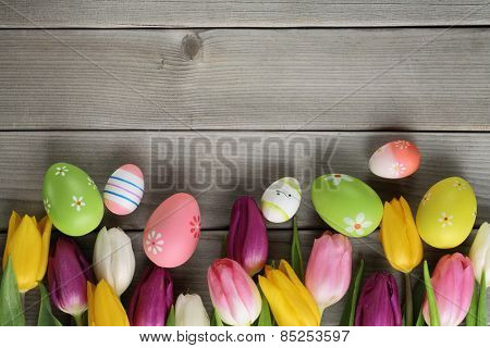 Easter eggs and tulips on wood background
