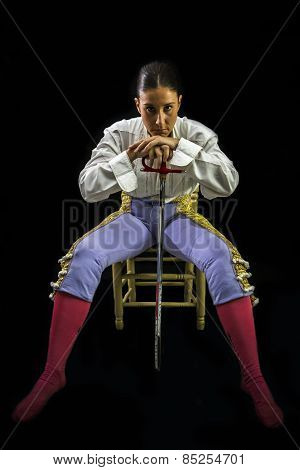 Woman Bullfighter Sitting On A Wooden Chair Holding A Sword