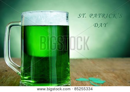 a glass mug with dyed green beer and a three-leaved shamrock on a wooden table, and the text st patricks day
