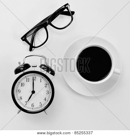 high-angle shot of a white table with a pair of black plastic-rimmed eyeglasses, and alarm clock and a cup of coffee