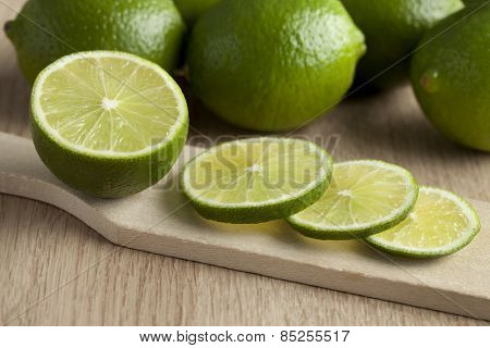 Fresh cut green limes on a cutting board