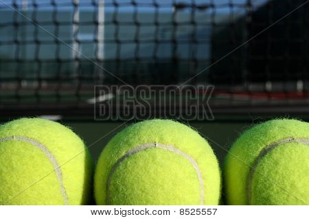 Three Tennis Balls With The Net In Background