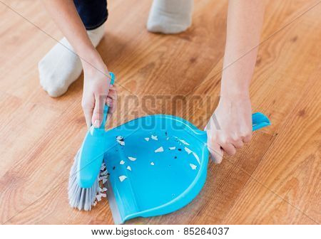 people, housework, cleaning and housekeeping concept - close up of woman with brush and dustpan sweeping floor at home