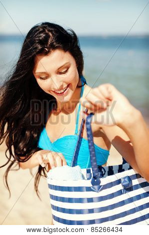 summer holidays, vacation and beach concept - girl in bikini with bag on the beach