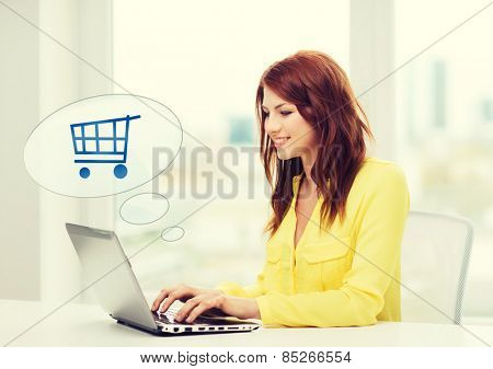 people, leisure and technology concept - smiling young woman with laptop computer and trolley icon shopping online at home