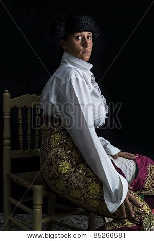 Woman Bullfighter Sitting On Black Background
