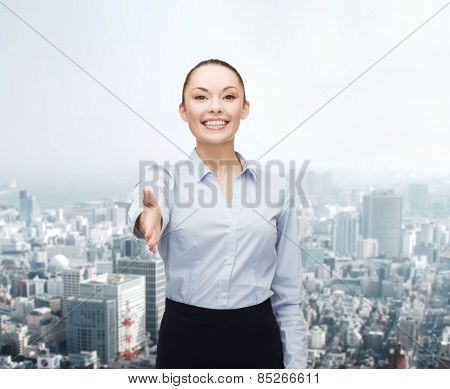 business, gesture and education concept - friendly young smiling businesswoman with opened hand ready for handshake