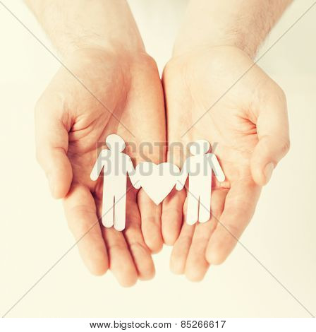 mans hands showing two paper men with heart shape