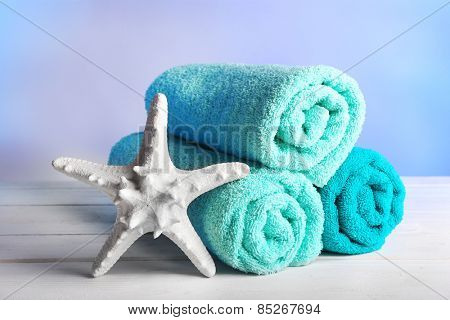 Rolled towels with starfish on wooden table and light colorful background