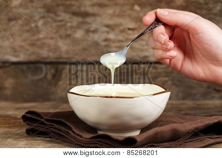 Bowl with condensed milk and spoon on napkin on wooden background