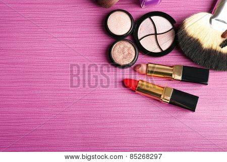 Set of colorful cosmetics on pink wooden table background