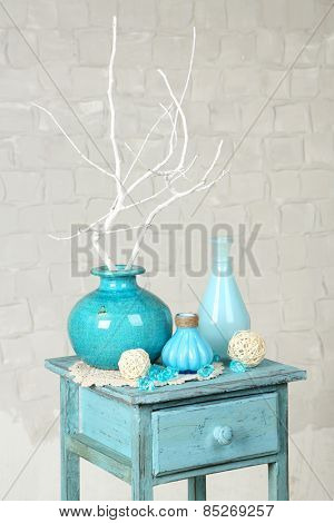 Interior with decorative vases and branch twig on nightstand and white brick wall background