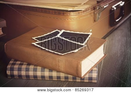 Vintage suitcase open with books on wooden background