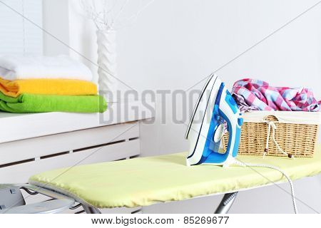 Iron and clothes on ironing board on interior background