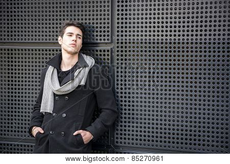 Young Man In A Winter Outfit Leaning On Metal Wall, Large Copyspace