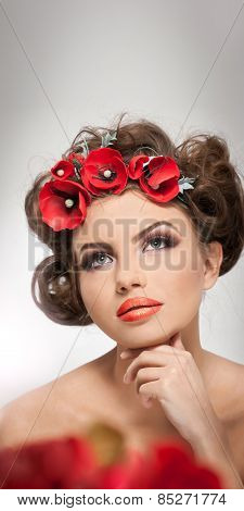 Portrait of beautiful girl in studio with red flowers in her hair and naked shoulders