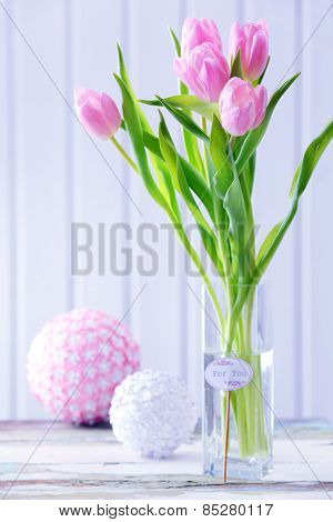 Beautiful pink tulips in vase with decorative balls on table on wooden background