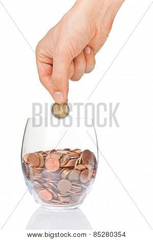 Hand Putting 2 Euro Into Glass With Euro Cents