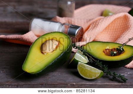 Sliced avocado with lime, salt and pepper on napkin on wooden background