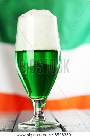 Glass of green beer on flag background