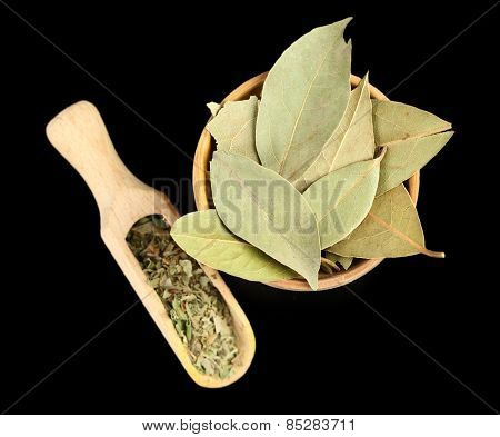 Bay leaves in wooden bowl, isolated on black