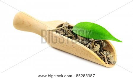 Wooden scoop with green tea with leaf isolated on white