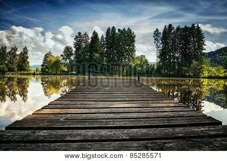 Wooden Footbridge In Front Of A Lake In Summer Season
