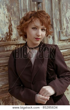Retro portrait of red haired women in vintage coat agains obsolete wooden background