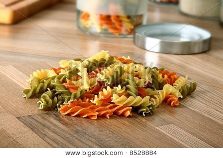Dry tricolor rotini pasta detail on wooden kitchen desk