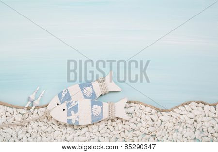 Blue or turquoise background with two wooden fishes and shells for a maritime decoration.