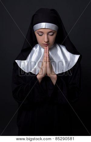 Young Beautiful Praying Nun Over Grey