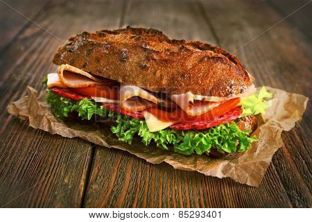 Fresh and tasty sandwich with ham and vegetables on paper on wooden background