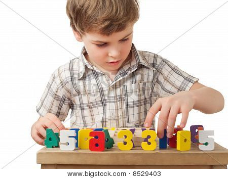 Boy In Checkered Shirt Displays Wooden Figures In Form Of Numerals On Table Isolated On White