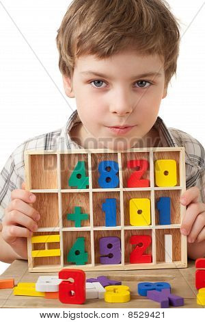 Boy In Checkered Shirt Plays In Wooden Figures In Form Of Numerals Isolated On White Background