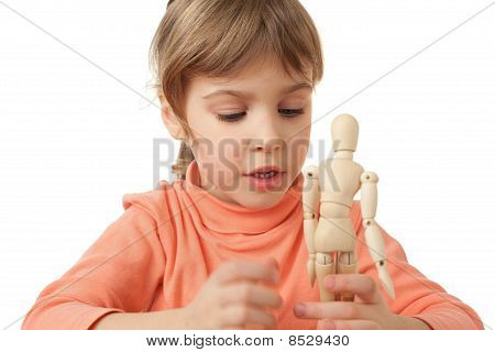 Pretty Little Girl Is Played By Wooden Little Manikin Isolated On White Background