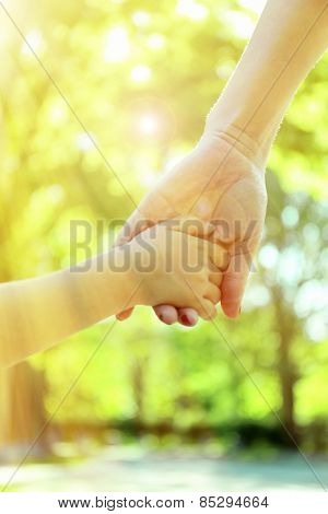 Mom and daughter hands on sunny nature background