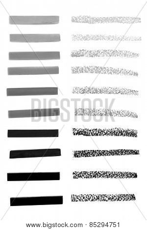 Charcoal drawing sticks in shades of grey with tester lines over white background.