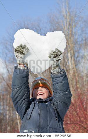 Junge hält In Händen Herz aus Schnee über Kopf im Winter In Holz