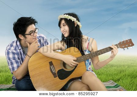 Happy Woman Playing Guitar At Field