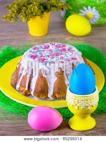 Multi-colored Eggs And Easter Cake On A Yellow Plate