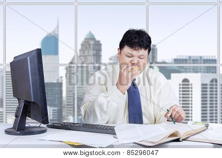 Hungry Manager Working While Eating Burger