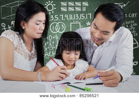 Little Girl Studying With Parents At Class