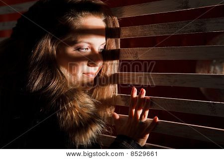 woman with her hair looks through the bars.