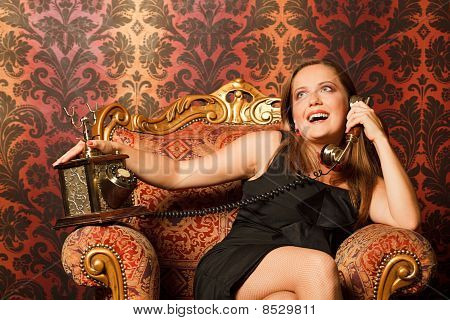 woman in black dress sitting on a vintage chair and talking on the old phone