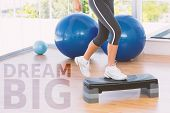 pic of step aerobics  - Low section of a fit woman performing step aerobics exercise against dream big - JPG