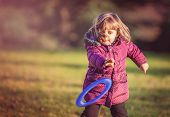 stock photo of frisbee  - Little girl throwing Frisbee in the park in autumn - JPG