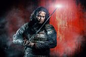 stock photo of swords  - Ancient male warrior in armor holding sword - JPG