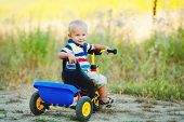 foto of tricycle  - A little boy with blond hair and gray eyes - JPG