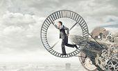 image of hamster  - Young businessman in suit running in hamster wheel - JPG