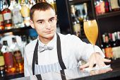 picture of bartender  - young barman worker at bartender desk serving coctail in restaurant bar  - JPG